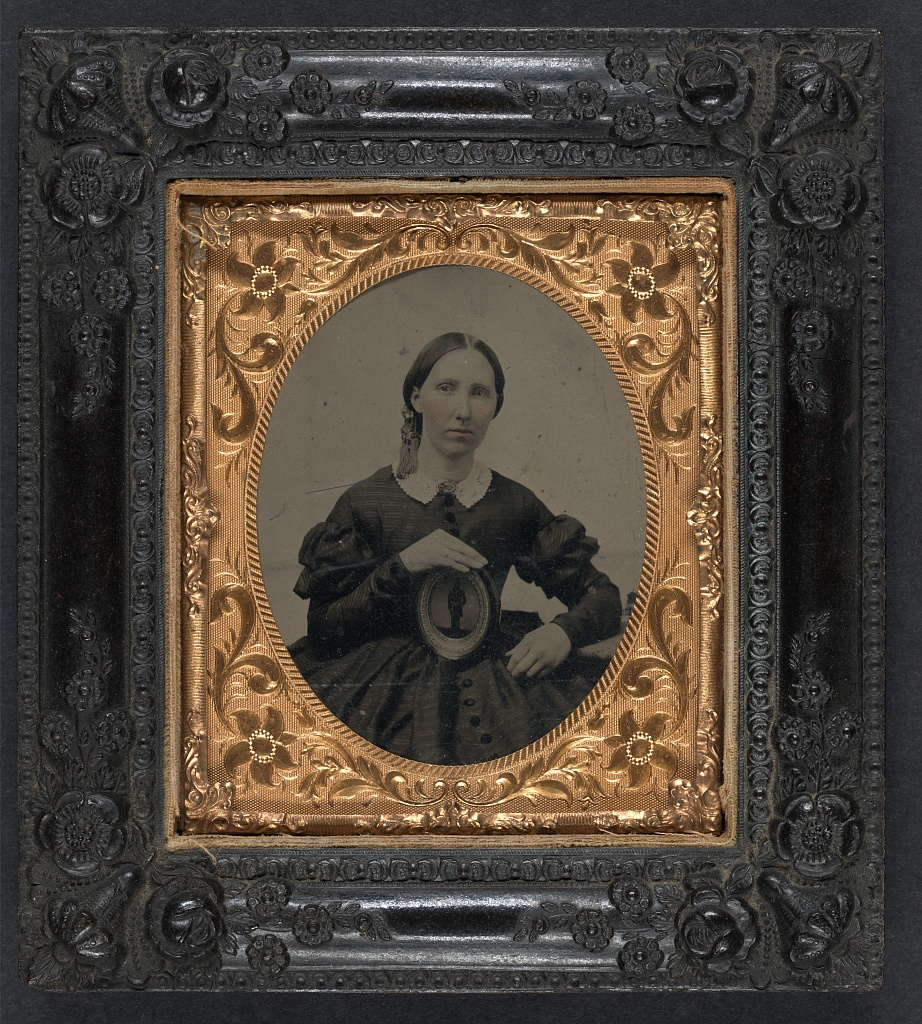 A woman in mourning clothes holding an image of a soldier (Library of Congress)